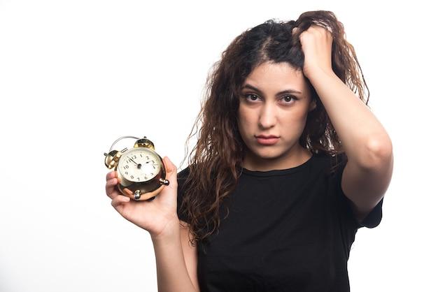 Femme avec horloge tenant sa tête sur fond blanc. photo de haute qualité