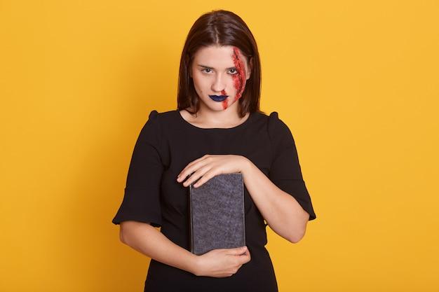 Femme avec horreur halloween maquillage et plaie sanglante qui pose en studio sur jaune, jeune femme avec vue honteuse détient livre avec incantation, robes robe noire