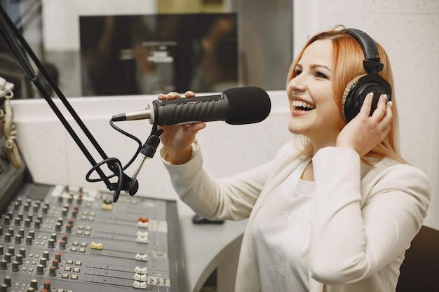 Femme hôte communiquant sur microphone. femme en studio de radio.