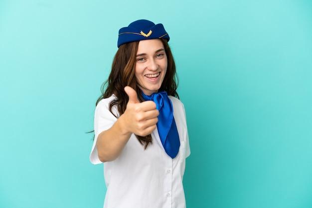 Femme hôtesse de l'air isolée sur fond bleu avec les pouces vers le haut parce que quelque chose de bien s'est produit