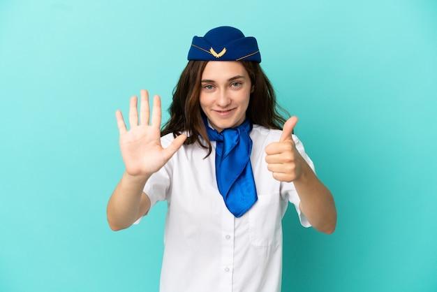 Femme hôtesse d'avion isolée sur fond bleu comptant six avec les doigts