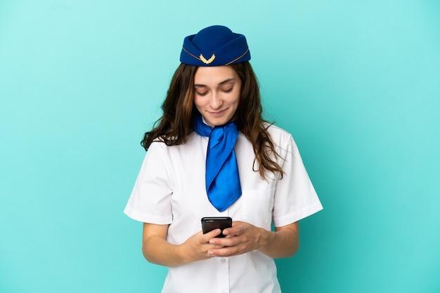 Femme hôtesse d'avion isolée sur fond bleu envoyant un message avec le mobile