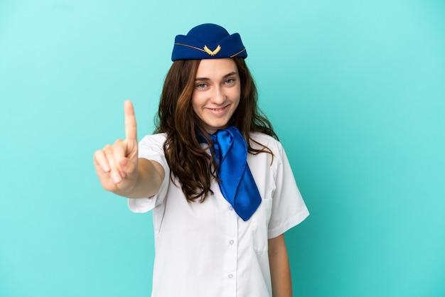 Femme hôtesse d'avion isolée sur fond bleu montrant et levant un doigt