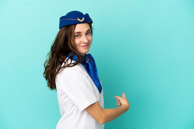 Femme hôtesse d'avion isolée sur fond bleu pointant vers l'arrière