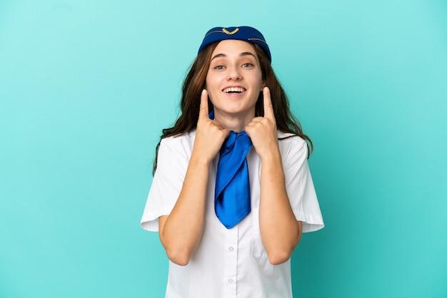 Femme hôtesse d'avion isolée sur fond bleu souriant avec une expression heureuse et agréable