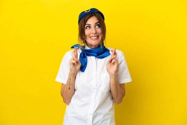 Femme hôtesse d'avion isolée sur fond jaune avec les doigts qui se croisent