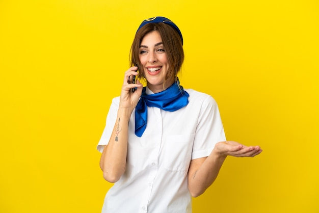Femme hôtesse d'avion isolée sur fond jaune en gardant une conversation avec le téléphone portable avec quelqu'un