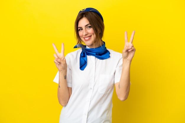 Femme hôtesse d'avion isolée sur fond jaune montrant le signe de la victoire avec les deux mains