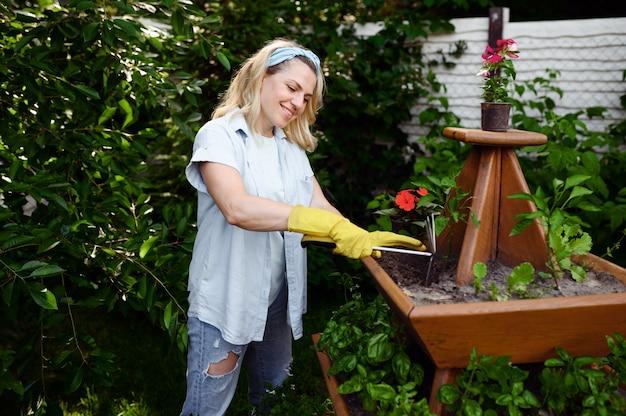 Femme avec houe au parterre de fleurs dans le jardin