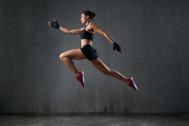 Femme humide forte posant pendant le saut