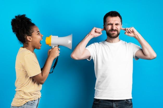 Femme hurlant à l'homme par mégaphone