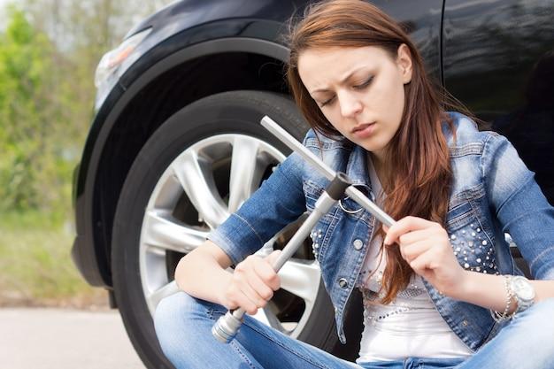 Femme ignorante fronçant les sourcils à une clé de roue alors qu'elle est assise sur la route à côté de sa voiture
