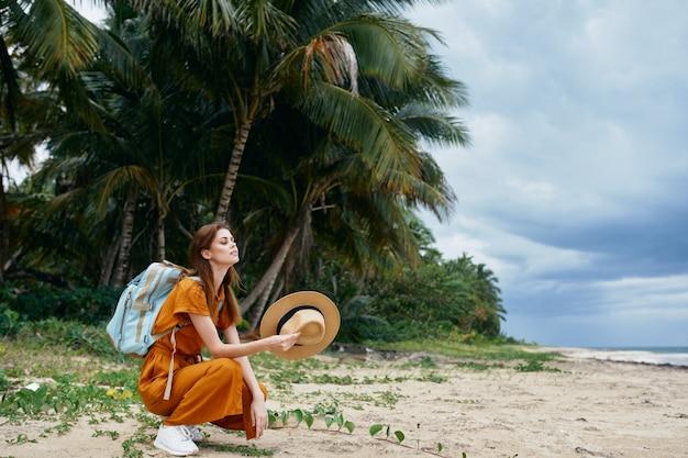 Femme sur l'île avec sac à dos voyage palmiers tropiques
