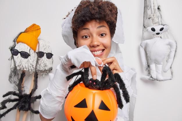 Une femme a une image effrayante tient une citrouille sculptée avec une grosse araignée noire se prépare pour la célébration d'halloween pose sur blanc croit au mystère attend pour une nuit horrible