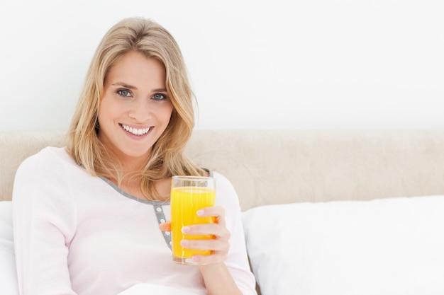 Femme avec impatience et souriant avec un verre de jus d'orange à la main