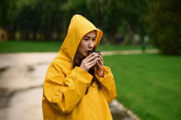 Femme en imperméable boit du thé chaud dans le parc d'été, jour de pluie. seule personne de sexe féminin en cape de pluie sur chemin de marche, temps humide dans la ruelle