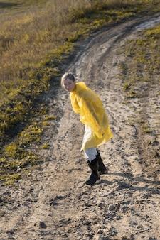 Femme en imperméable jaune glissant sur une route de campagne boueuse
