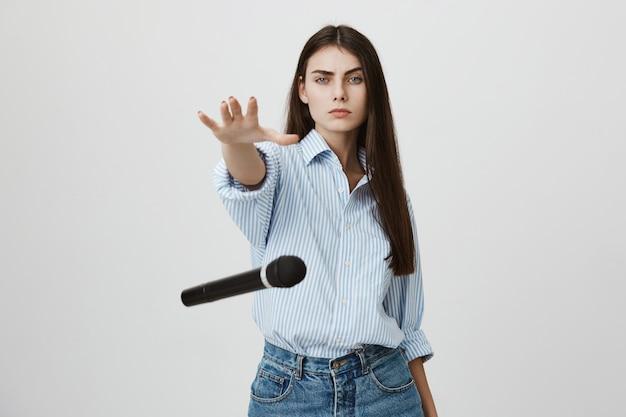 Femme impertinente confiante laisse tomber le microphone