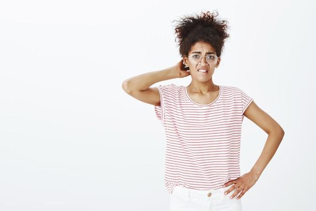 Femme incertaine en difficulté avec une coiffure afro posant dans le studio