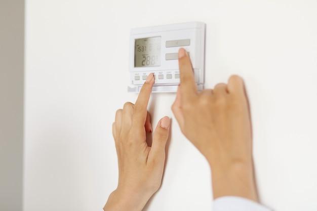 Femme inconnue utilisant un appareil électroménager connecté à la technologie de la maison intelligente sur le mur, surveillant le système de chauffage de sécurité énergétique, contrôle numérique dans l'appartement.