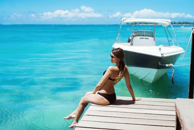 Femme incroyable en bikini se détendre sur la jetée à la recherche de suite