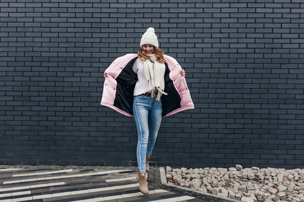 Femme incroyable en tenue d'hiver danse drôle sur rue urbaine. modèle féminin en jeans bénéficiant d'une séance photo par temps froid.