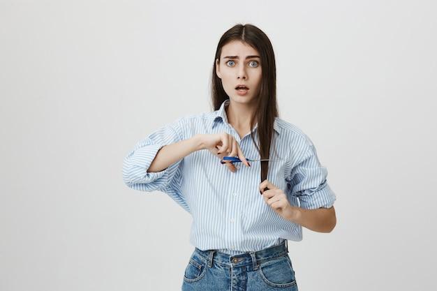 Femme indécise coupant les pointes fourchues avec des ciseaux, l'air inquiet