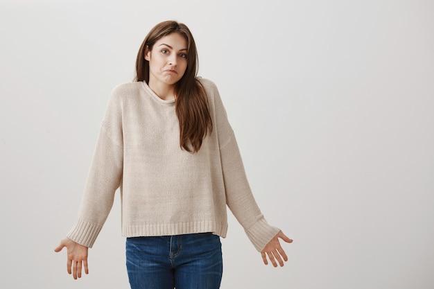 Femme indécise haussant les épaules et écartant les mains sur le côté sans aucune idée, ne sait rien