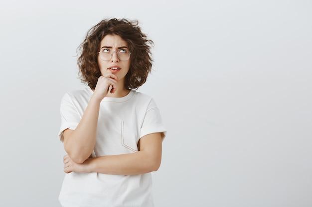Femme indécise et perplexe faisant des calculs, levant les yeux tout en pensant