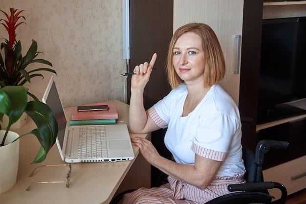 Une femme indépendante, handicapée dans un fauteuil roulant, travaille à distance de la maison sur un ordinateur portable, tenant un stylo dans sa main