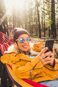 Une femme indépendante heureuse sourit et fait un appel vidéo dans un parc naturel en plein air - des personnes itinérantes et connectées dans les bois de la forêt avec la technologie d'itinérance en ligne - une jeune femme profite de vacances