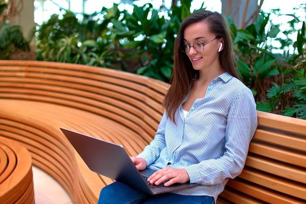 Femme indépendante moderne intelligente travaillant à distance en ligne sur un ordinateur