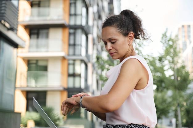 Femme indépendante occupée vérifiant l'heure sur les mains pendant qu'elle se repose en ville, assise sur un banc en bois de la rue pendant la pause-café