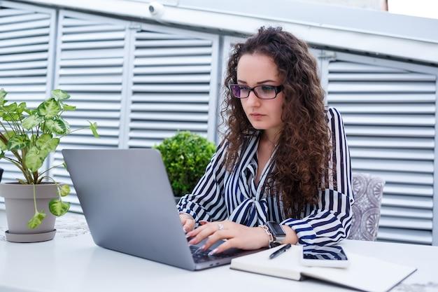 Femme indépendante pensive dans des vêtements décontractés à la mode travaillant avec un ordinateur portable et prenant des notes, souriant et regardant la terrasse extérieure du café