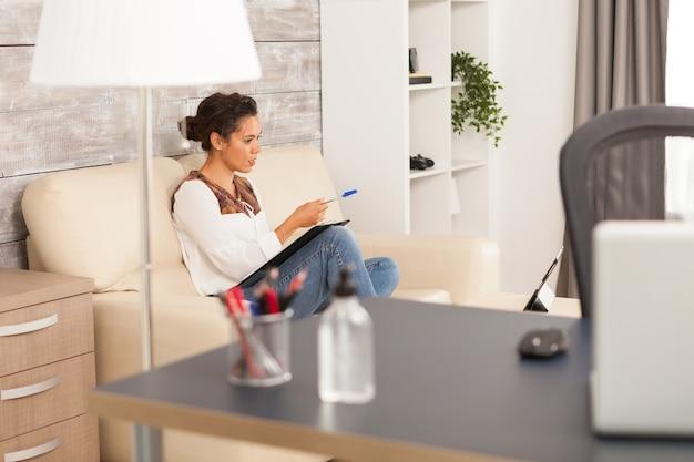 Femme indépendante pointant sur un ordinateur portable tout en travaillant à domicile.