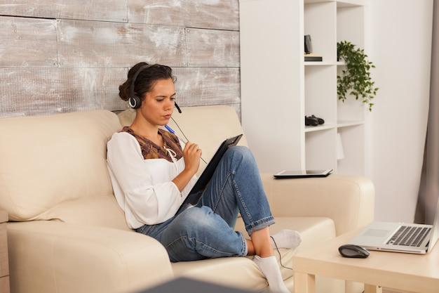 Femme indépendante portant des écouteurs lors d'une vidéoconférence tout en travaillant à domicile.
