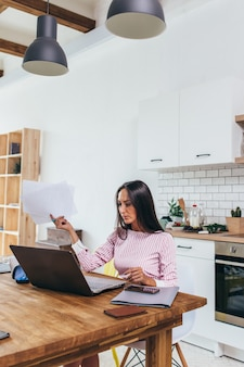 Femme indépendante regardant des documents et utilisant un ordinateur portable pour le travail.