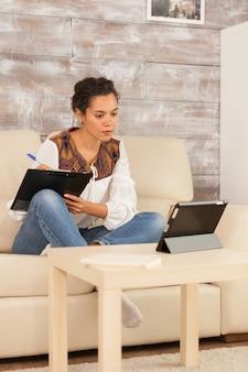 Femme indépendante réussie travaillant à domicile lors d'un appel vidéo avec des partenaires commerciaux.