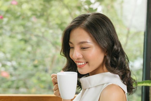 Femme indépendante tenant une tasse de café et utilisant un ordinateur portable sur une table dans un café-café