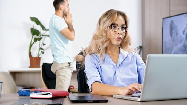Femme indépendante travaillant sur l'ordinateur portable dans la maison pendant que le mari regarde la télévision en arrière-plan