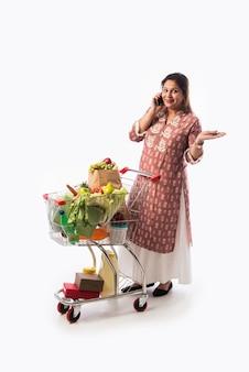 Femme indienne d'âge moyen avec panier ou chariot plein d'épicerie, de légumes et de fruits. photo pleine longueur isolée sur mur blanc