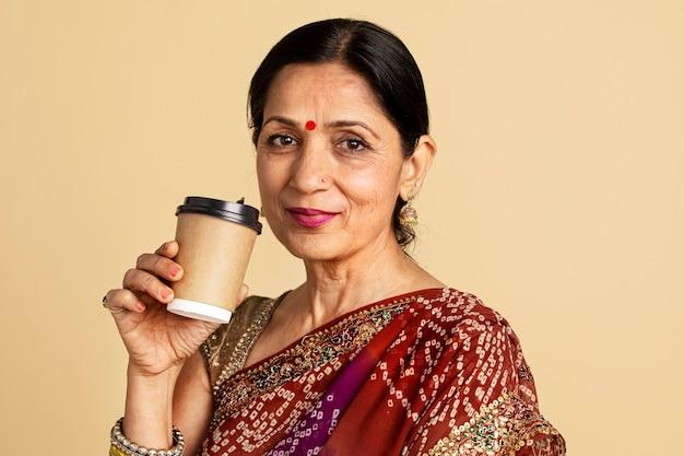 Une femme indienne dans un sari boit du café à partir d'une maquette de tasse en papier