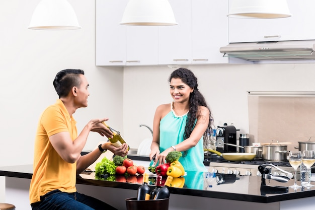 Femme indienne et homme en cuisine avec du vin rouge