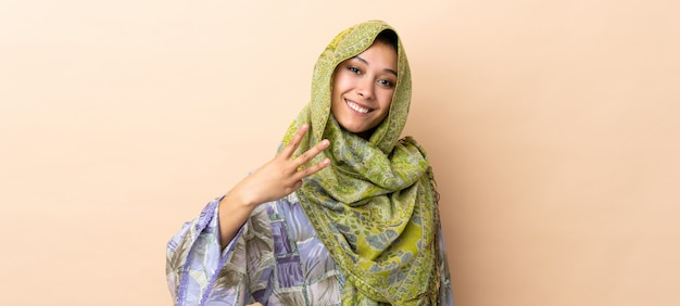 Femme indienne isolée sur beige heureux et en comptant trois avec les doigts