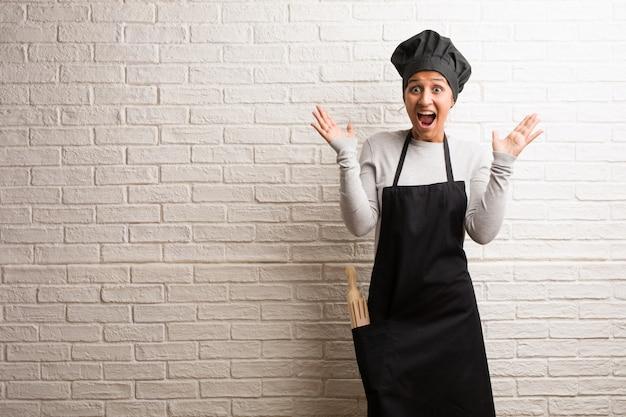 Femme indienne jeune boulanger contre un mur de briques crier heureux.