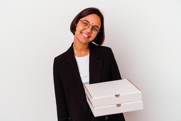 Femme indienne jeune entreprise tenant des pizzas isolé heureux, souriant et gai.