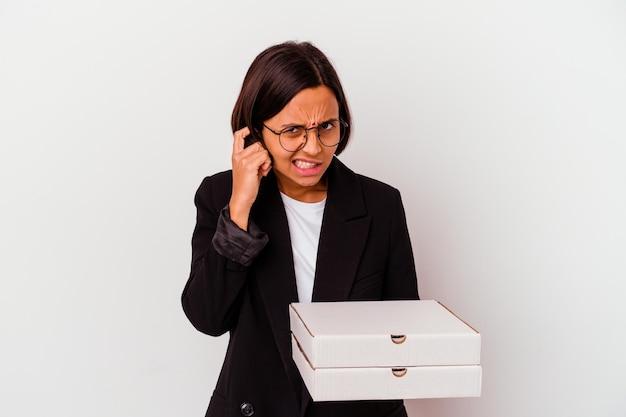 Femme indienne jeune entreprise tenant des pizzas isolées couvrant les oreilles avec les mains.