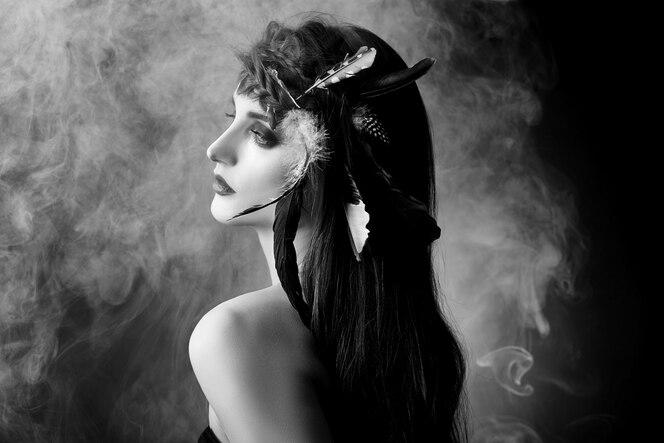Femme indienne avec des plumes dans les cheveux, portrait de la beauté amérindienne sur fond sombre en fumée. beau visage avec une peau propre, maquillage contrasté