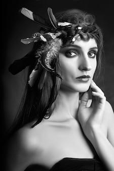 Femme indienne avec des plumes dans les cheveux, portrait de la beauté de la femme amérindienne en fumée. beau visage avec une peau propre, maquillage contrasté