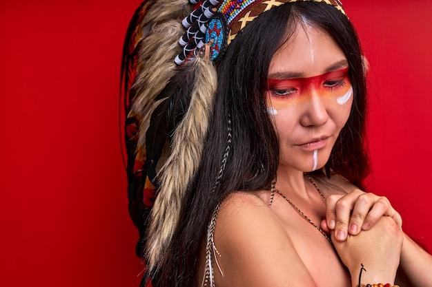 Femme indienne réfléchie en contemplation, regardant vers le bas. jeune femme avec des peintures de chaman sur le visage isolé